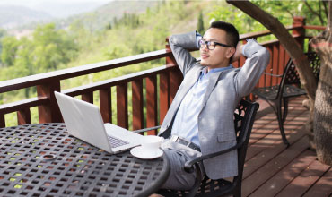 Businessman relaxing at table with laptop & coffee