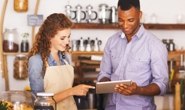 man and woman in store using tablet for business