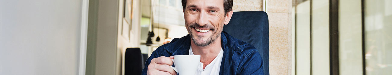 Man drinking coffee and smiling